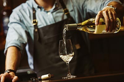 male sommelier pouring white wine into long stemmed wineglasses.